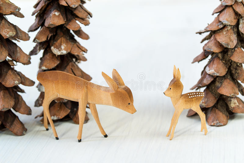 Toy wooden deer and pine cones in the form of christmas trees. On a white wooden background royalty free stock photos