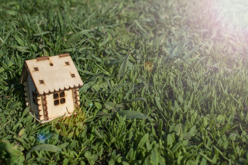 Toy wooden house on the bright grass. Sun glare on the right side. Copy space. Real estate concept, business loan financing royalty free stock photography