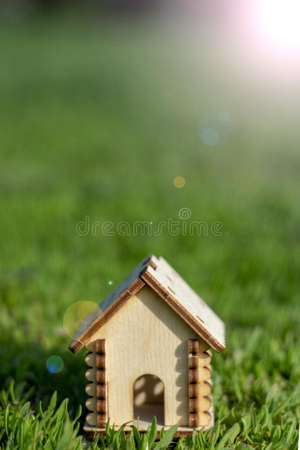 Toy wooden house on the bright grass. Sun glare on the right side. Copy space. Real estate concept, business loan financing royalty free stock images