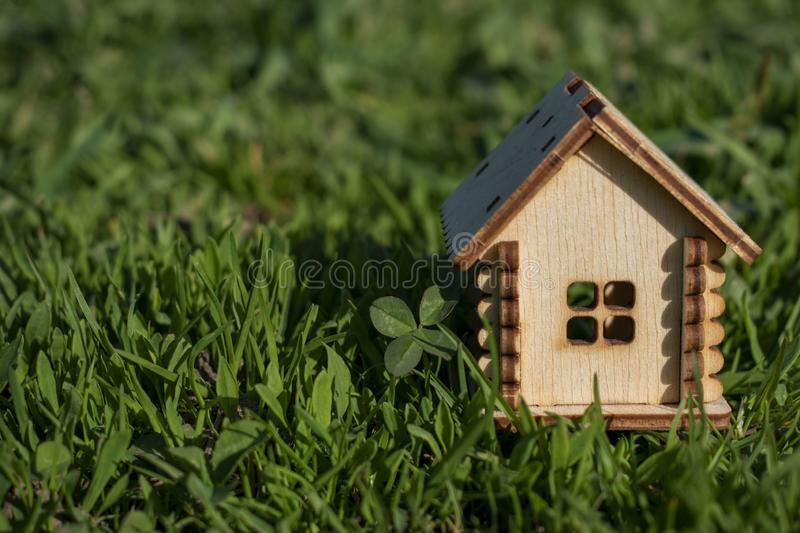 Toy wooden house on the bright grass in sunny weather. Copy space. Real estate concept, business loan financing concept, new house stock image