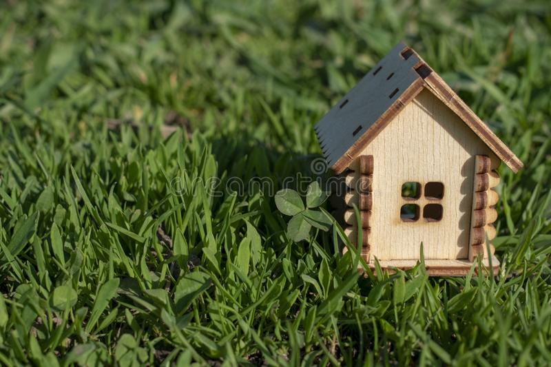 Toy wooden house on the bright grass in sunny weather. Copy space. Real estate concept, business loan financing concept, new house stock photography