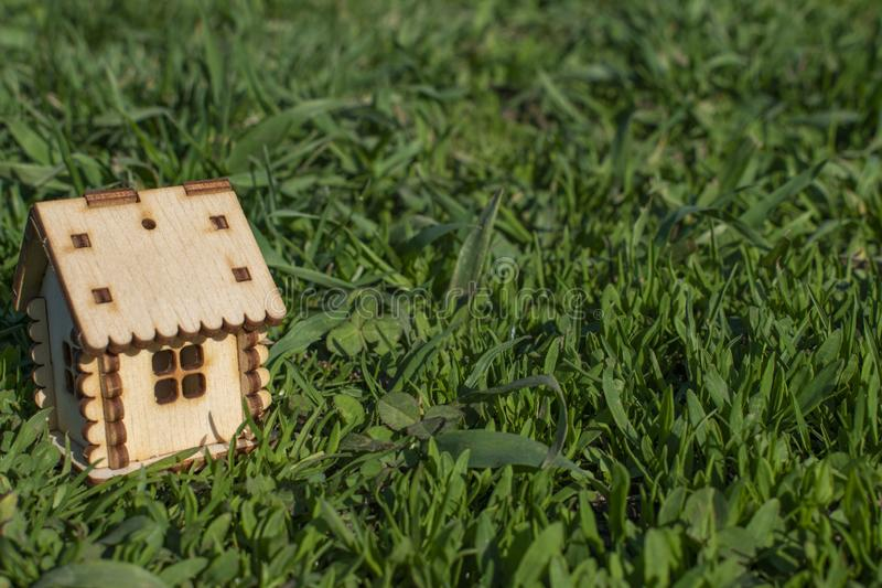 Toy wooden house on the bright grass in sunny weather. Copy space. Real estate concept, business loan financing concept, new house royalty free stock images