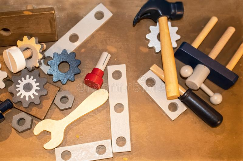 Toy wooden toy tools including gears and a wrench and hammer scattered on a wooden surface - top lay stock image
