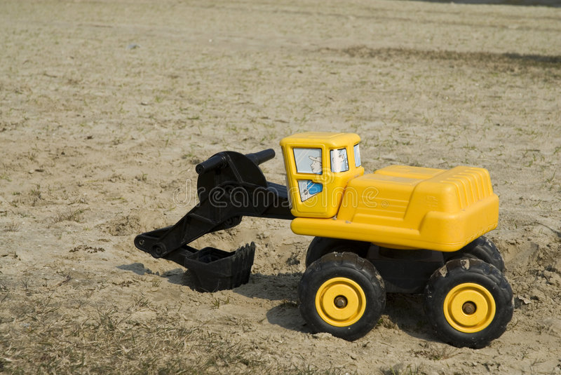 Toy Yellow Bulldozer. Yellow Toy Bulldozer in the sand stock photography