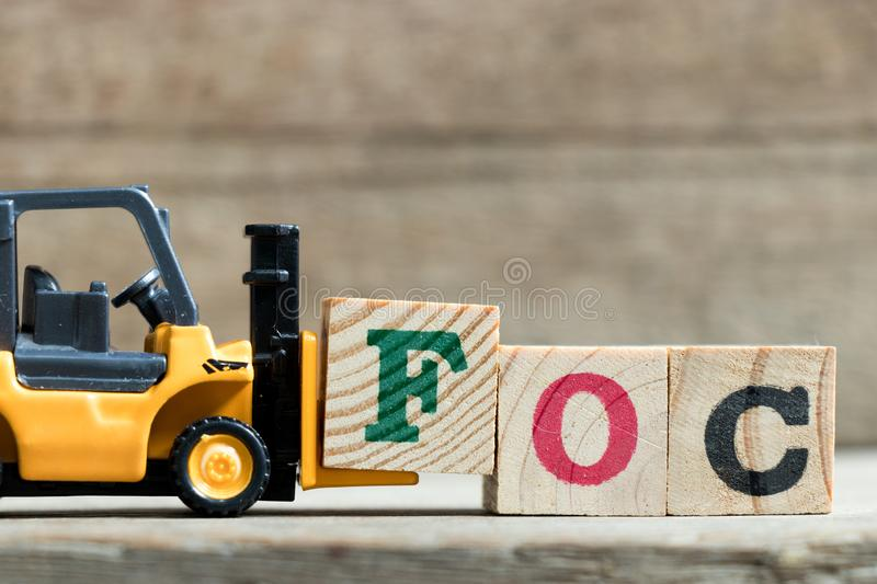 Toy yellow forklift hold letter block F to complete word FOC Abbreviation of Free of charge royalty free stock photo