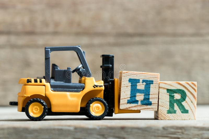 Toy yellow forklift hold letter block H to word HR. Toy yellow forklift hold letter block H to complete word HR Abbreviation of Human resourceon wood background royalty free stock photography