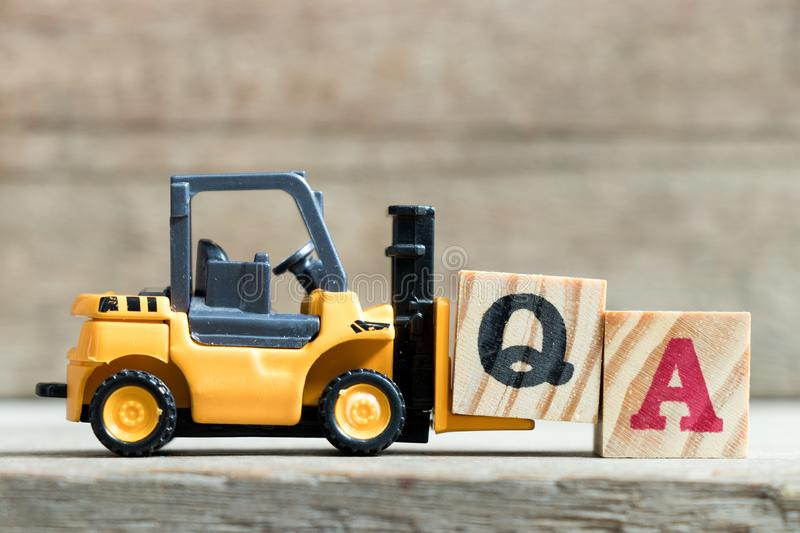 Toy yellow forklift hold letter block Q to complete word QA Abbreviation of Quality Assurance. On wood background stock photo
