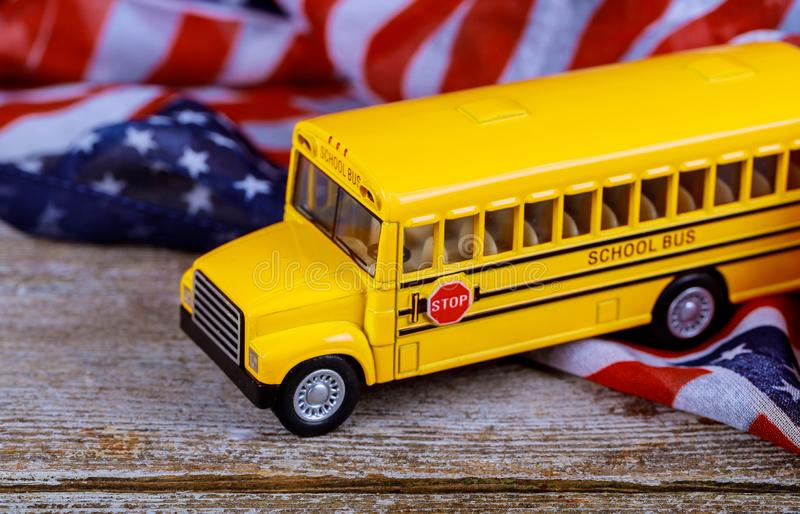 Toy yellow school bus on american flag royalty free stock image