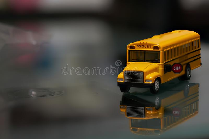 Toy yellow school bus on glass with reflection royalty free stock images