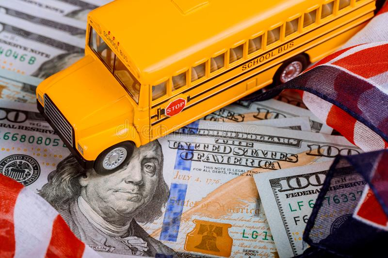 Toy yellow school bus and US flag, dollar cash money. Toy yellow school bus , US flag and dollar cash money royalty free stock photography