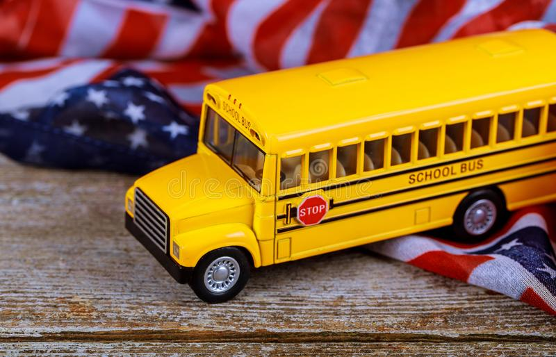 Toy yellow school bus and US flag. Toy yellow school bus taking school and US flag royalty free stock photography