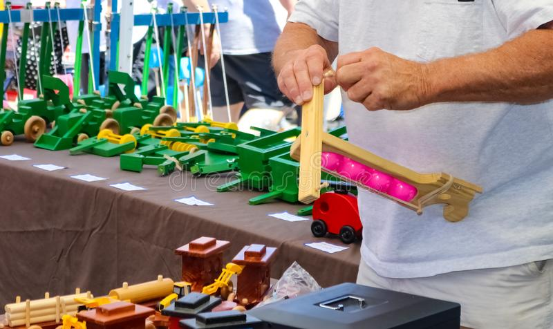 Toymakers hands putting together a wooden toy in a booth at out outside festival royalty free stock photo