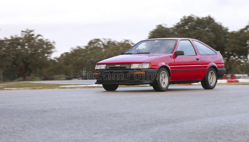 Toyota Corolla GT hermana la leva AE86 que deriva en circuito de carreras imagen de archivo