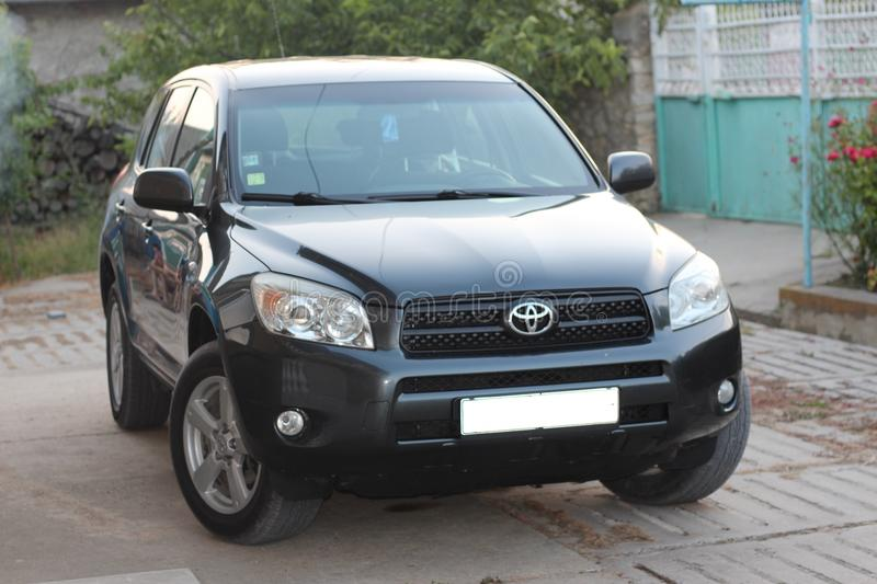 Toyota RAV4 XA30. Front and right side view on a black third generation Toyota RAV4, XA30, 2006 model year, parked in front of a green country style metal gate royalty free stock photo