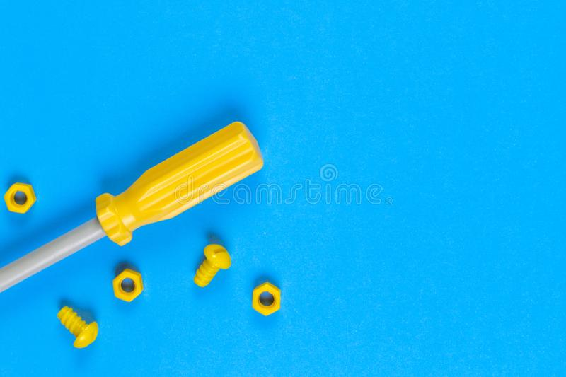 Toys background. Kids construction toys tools on light blue and yellow background. Top view stock image