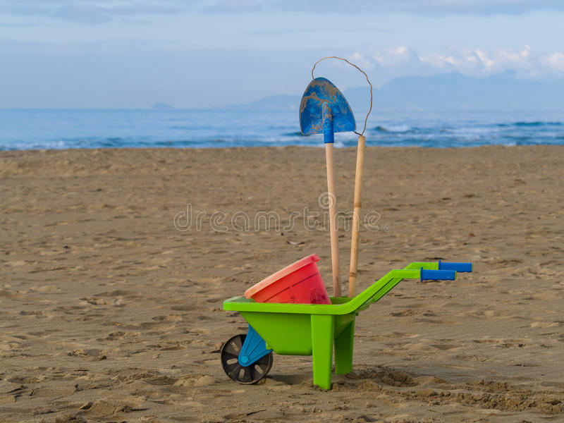 Toys on the beach plastic wheelbarrow, bucket and spade. Sky and sea in background royalty free stock photography