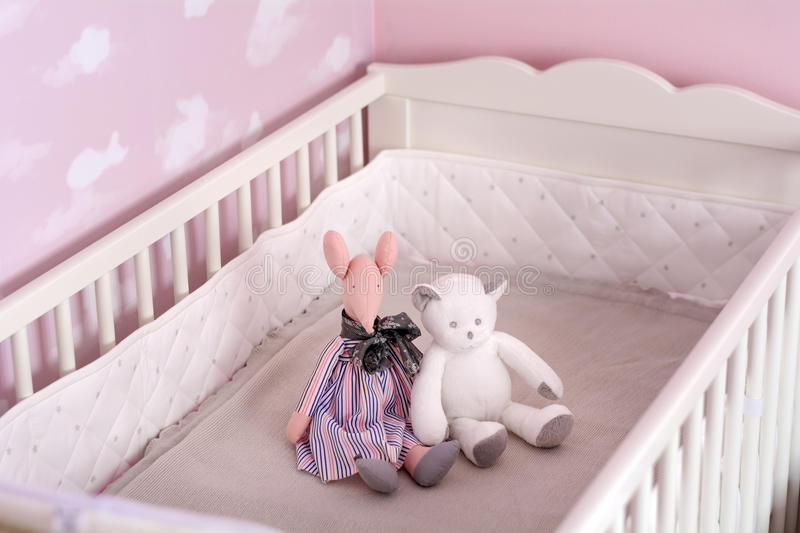 Toys on a bed in a baby pink room royalty free stock photography