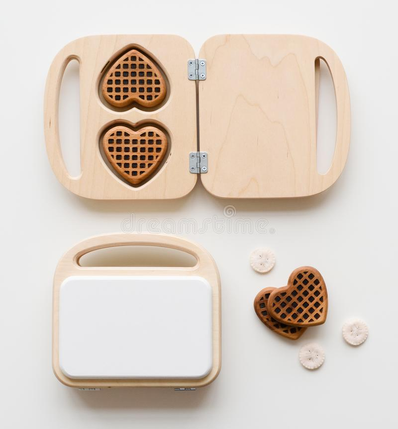 Toys for children play kitchen. Wooden waffle maker and heart shape waffles on white background top view stock images