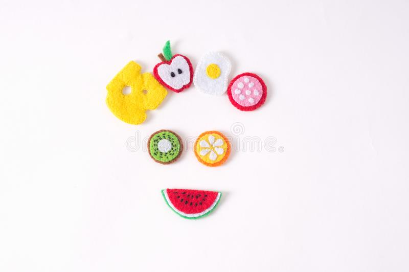 Toys in the form of food and fruits hand made of felt on a white stock photography