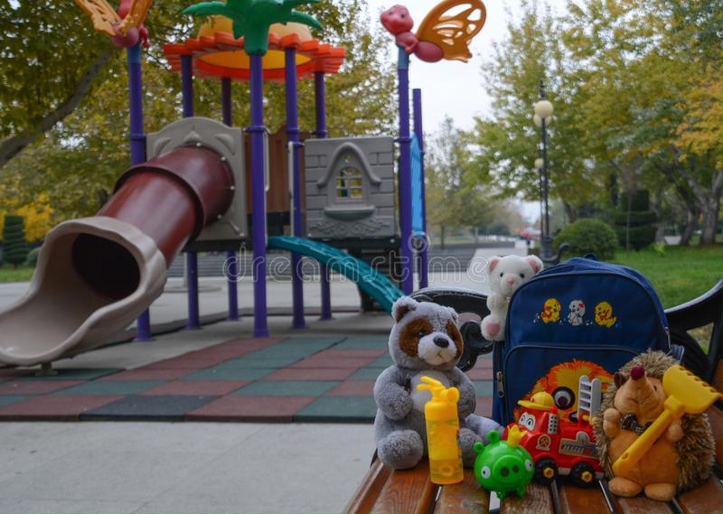 Toys & Playground. Playground in park & lovely toys on bench royalty free stock photo