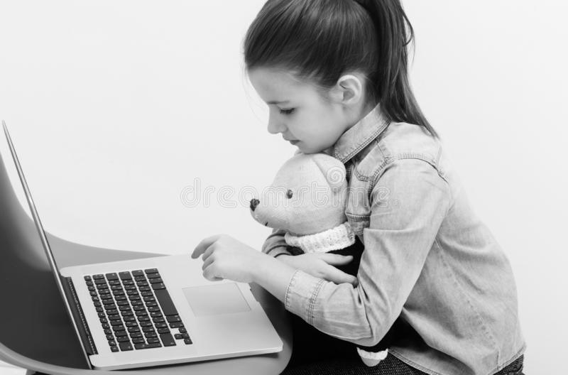 Adorable girl hugging cute teddy bear and typing on laptop royalty free stock images