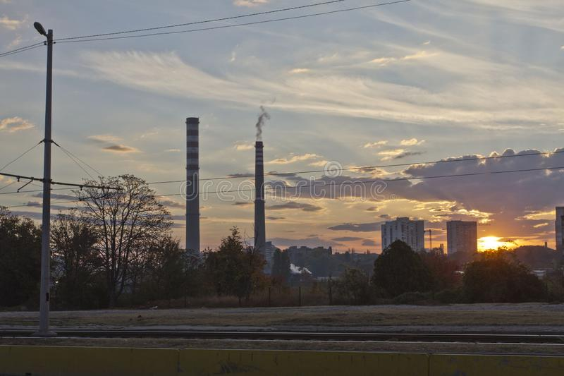 TPP thermal power plant on a sunrise. Refinery with smokestacks. Smoke from factory pollutes the environment. High red and white t stock photo