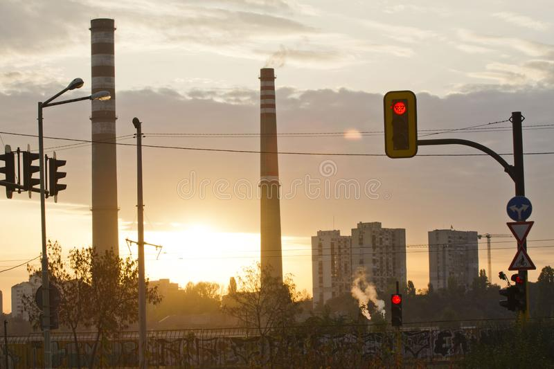 TPP thermal power plant on a sunrise. Refinery with smokestacks. Smoke from factory pollutes the environment. High red and white t stock image