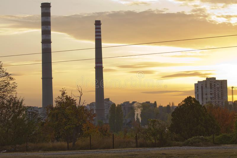 TPP thermal power plant on a sunrise. Refinery with smokestacks. Smoke from factory pollutes the environment. High red and white t royalty free stock photos