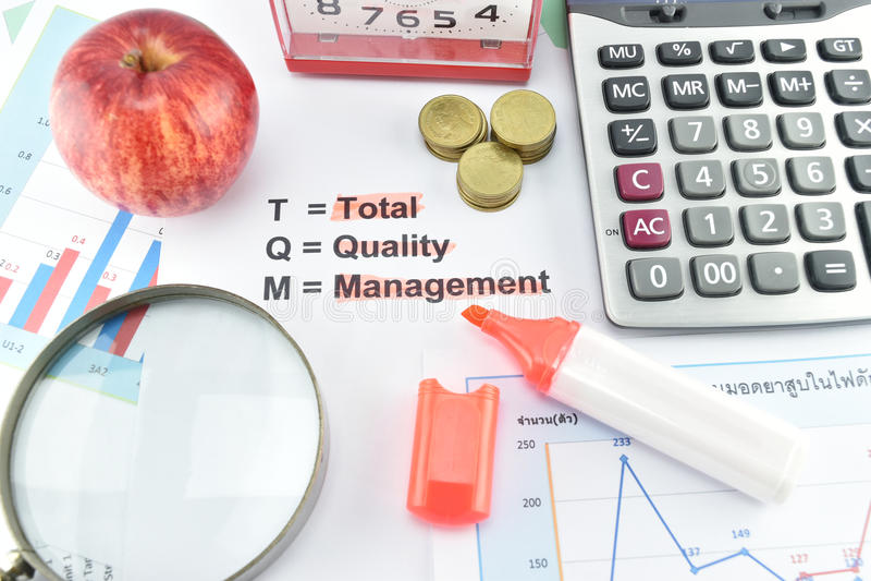TQM的意思与文件,金钱,时钟,苹果的计算器的 免版税库存照片