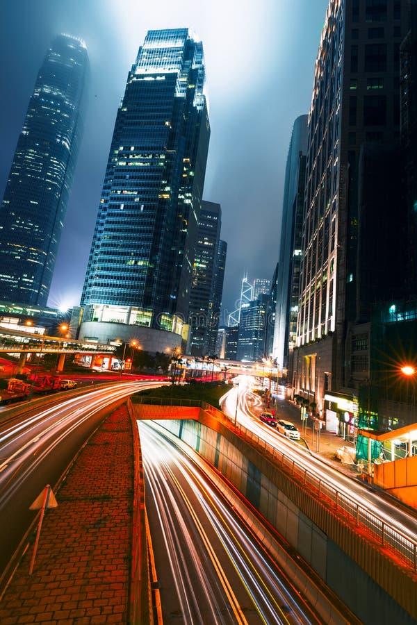 Tráfego da rua no por do sol crepuscular em Hong Kong Construções do arranha-céus do escritório e com as fugas borradas da luz do foto de stock royalty free