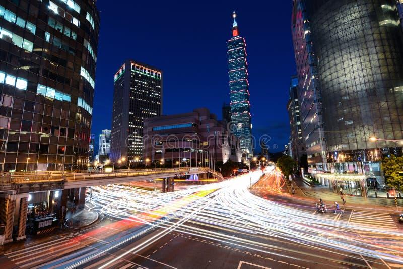Tráfego das horas de ponta que apressa-se através de uma interseção ocupada perto de Taipei 101 na capital de Taiwan foto de stock royalty free