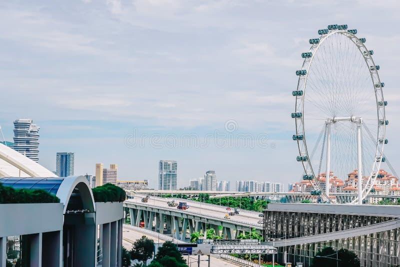 Tráfego de carros na avenida de Sheares com a roda de ferris gigante do inseto de Singapura no fundo imagens de stock