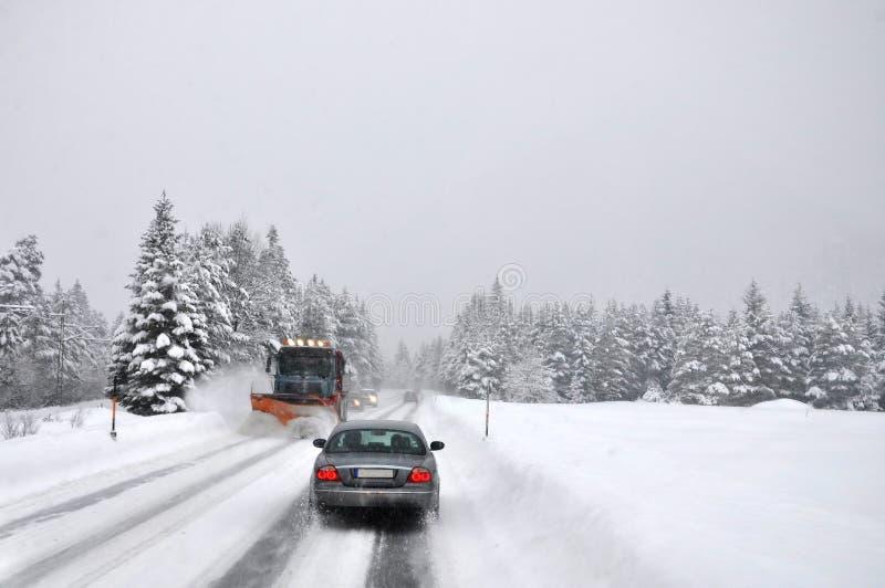 Tráfego difícil após nevar O líquido de limpeza da neve limpa operativamente a estrada coberto de neve da montanha imagem de stock royalty free