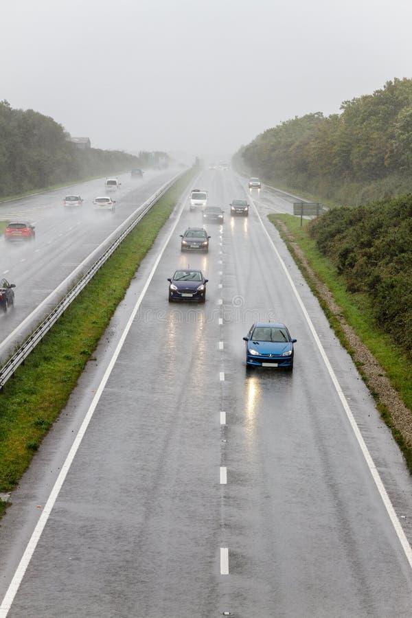 Tráfego que conduz na chuva no caminho duplo fotos de stock