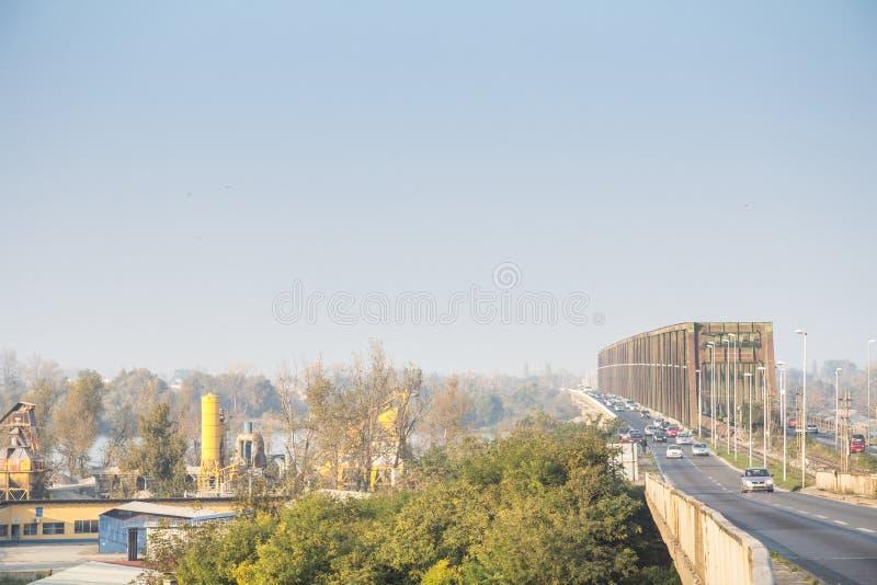 Tráfico de coche denso que pasa por el Pancevacki más, o puente de Pancevo, durante un día de mala calidad del aire atmosférica c fotos de archivo libres de regalías