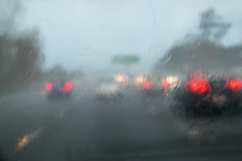 Tráfico de coche que conduce con fuertes lluvias en el parabrisas del coche - indique hola imagenes de archivo