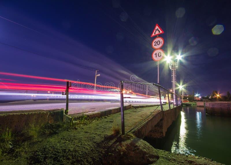 Tráfico de la noche sobre el puente viejo foto de archivo