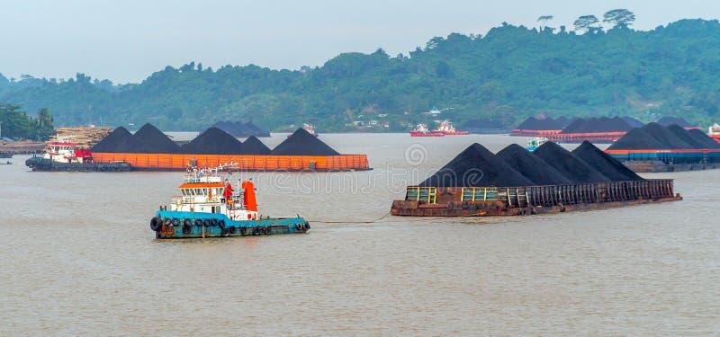 Tráfico de los remolcadores que arrastran la gabarra del carbón en el río de Mahakam, Indonesia imagen de archivo libre de regalías
