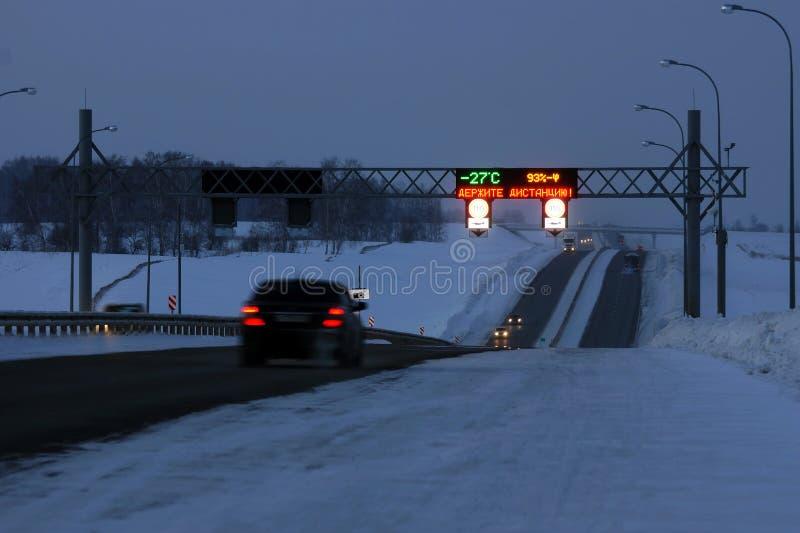 Tráfico en una carretera oscura en invierno foto de archivo