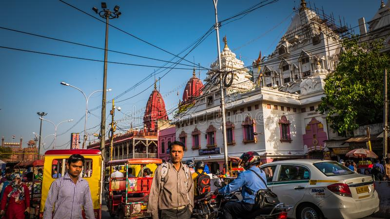 Tráfico ocupado y gente en el centro de la ciudad del mercado de Chandni Chowk en Delhi vieja, la India con el fuerte rojo foto de archivo libre de regalías