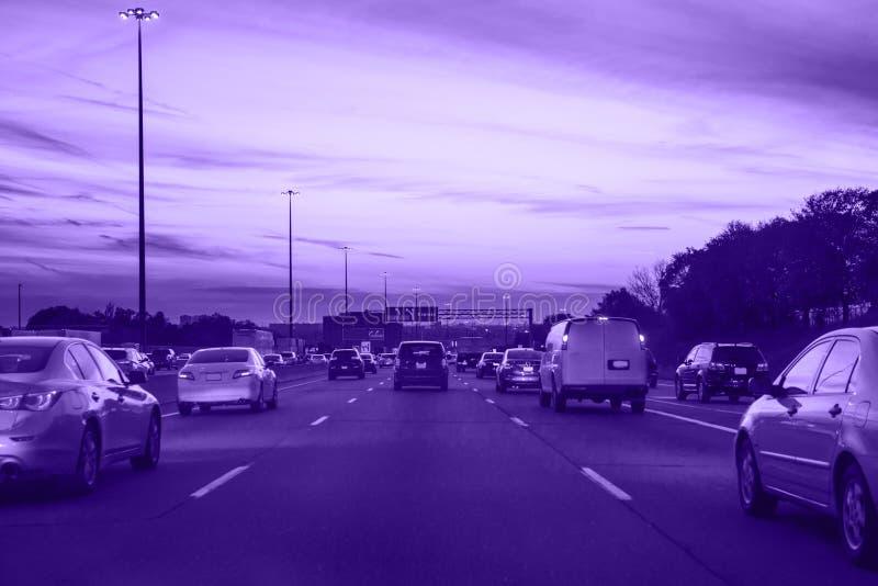 Tráfico ultravioleta, coches en el camino de la carretera el noche de la tarde en ciudad ocupada fotos de archivo libres de regalías