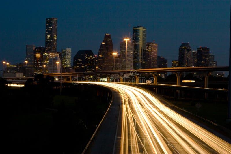 Tráfico y el horizonte de la ciudad en la noche fotografía de archivo