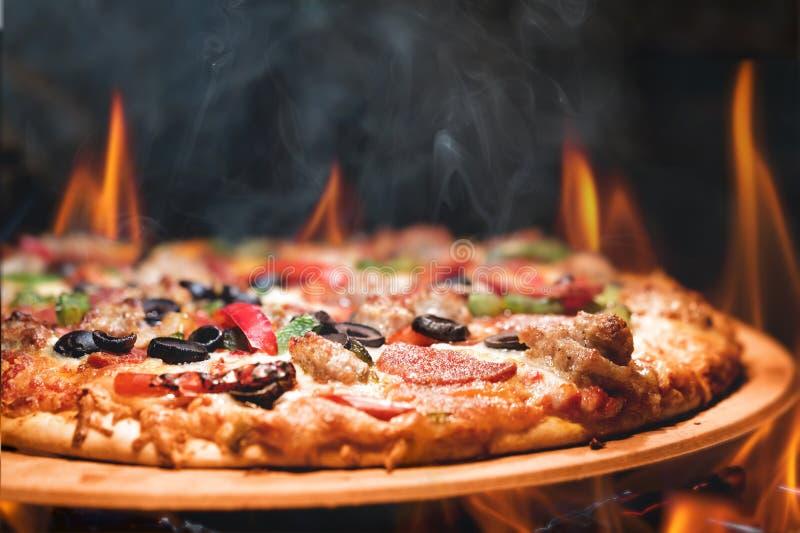Trä avfyrad pizza med flammor arkivbilder