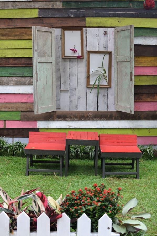 Trä bordlägga och stolar i trädgård royaltyfri bild