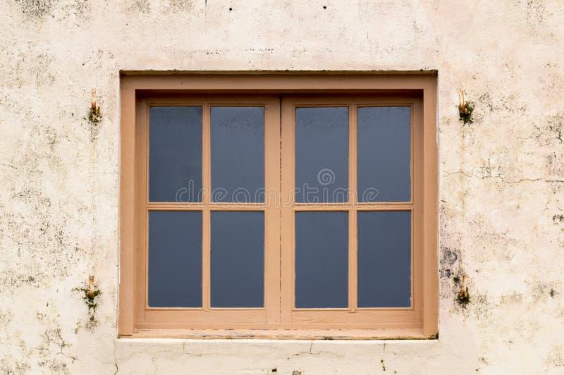 Trä inramade fönster på murbrukväggen royaltyfri fotografi