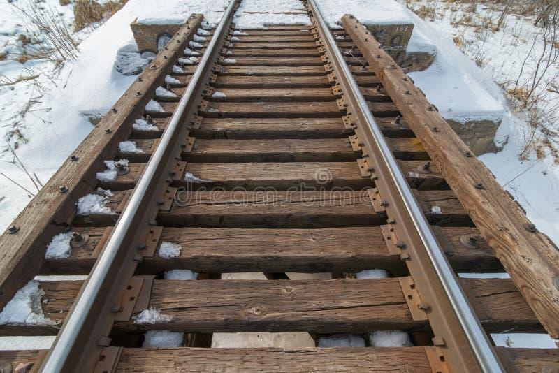 Trä och ståljärnvägbro i den lantliga snöig kalla Minnesota vintern arkivbilder