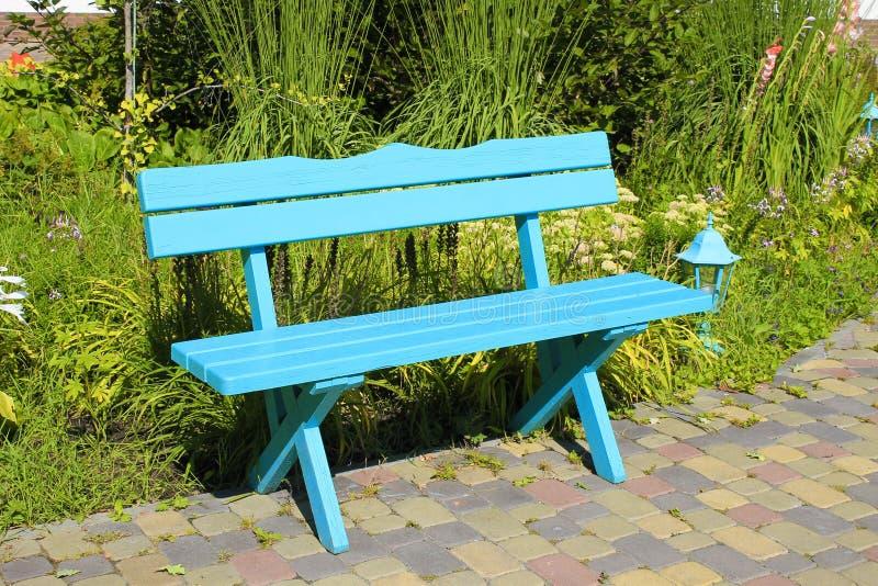 Trä parkera bänken på sommarträdgården arkivfoton