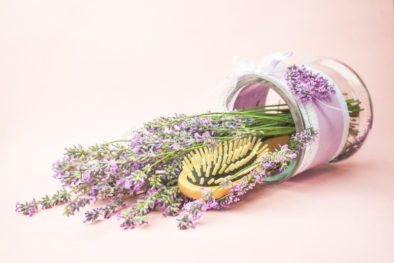 Trä skalpera och massera borste- och hårhårkammen med lavendelblommor på pastellfärgad rosa bakgrund fotografering för bildbyråer