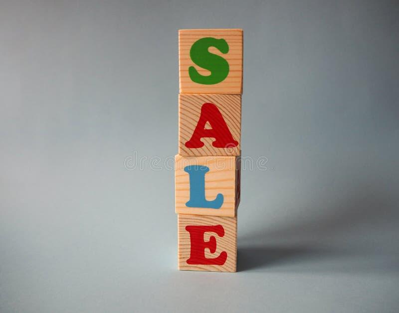 Träalfabetleksakkvarter med texten: försäljning Isolerade ungar mång--färgade abckuber på blå bakgrund med kopieringsutrymme fotografering för bildbyråer