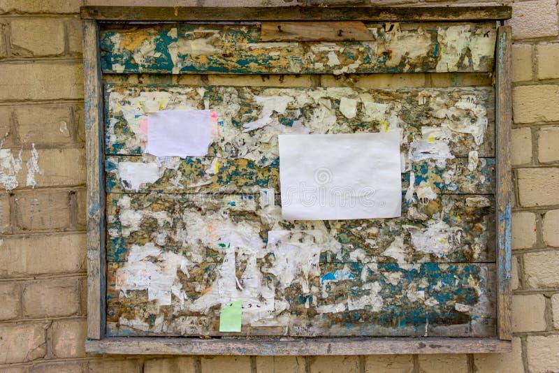 Träanslagstavla på en vit tegelstenvägg Gammalt målat trä med rester av pappers- annonser Mellanrum för pappers- annonsering ?tl? arkivbilder